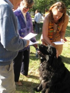 Rev. Martha Clark blessed a large black dog, one of many neighborhood dogs who attended the Blessing of the Animals last year.  (Photo: Elaine F. Graves)