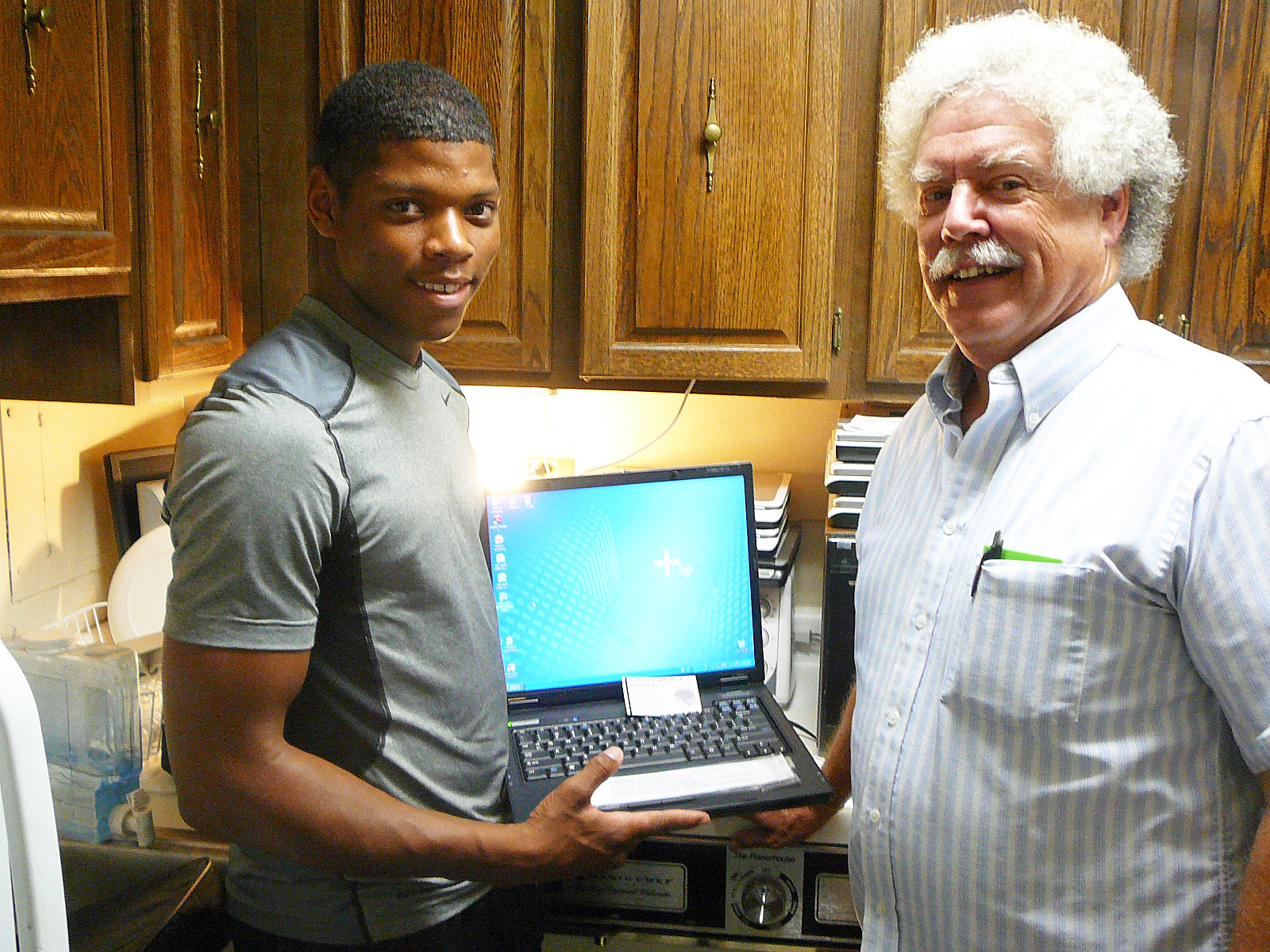 Greenleaf Gardens resident Marlon Mitchell received a notebook computer as part of his scholarship from the Southwest Neighborhood Assembly. He is entering his freshman year at Kent State University. The computer was one of several reconditioned by SWNA's two computer technology interns, Andre Wilkinson and Duane Patterson, both of whom also happen to live at Greenleaf Gardens. (Photo by Perry Klein)