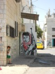 A Palestinian girl stands near mural of female combatant