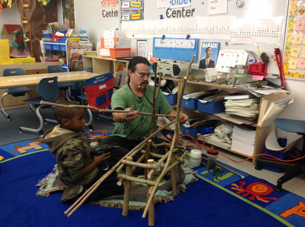 Willow Bill and a young assistant work on a nearly life-size reindeer made of willow branches.